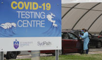 People wait at a drive through COVID-19 testing station at a beach in Sydney, Australia, Saturday, Dec. 19, 2020. Sydney's northern beaches will enter a lockdown similar to the one imposed during the start of the COVID-19 pandemic in March as a cluster of cases in the area increased to more than 40. (AP Photo/Mark Baker)