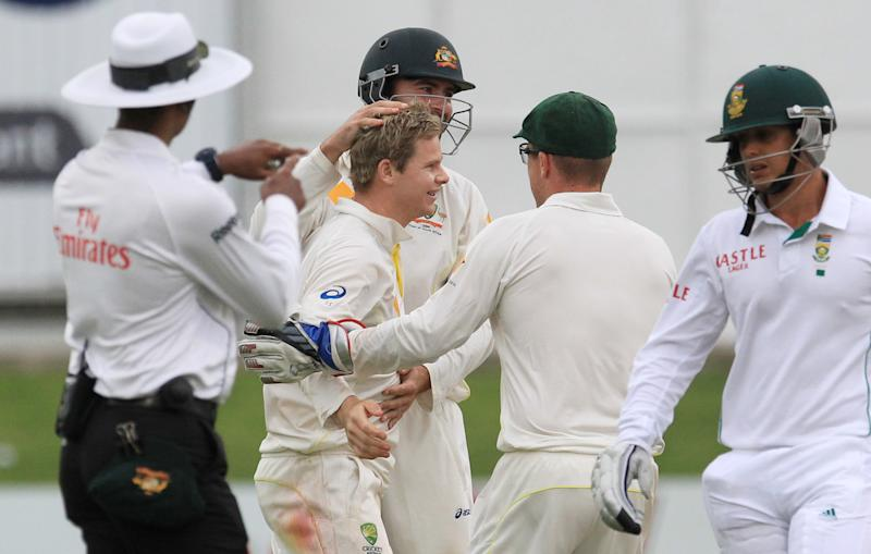 Australia's bowler Steven Smith, second left, celebrates with teammates after dismissing South Africa's batsman Quinton de Kock, right, for 7 runs on the first day of their 2nd cricket test match at St George's Park in Port Elizabeth, South Africa, Thursday, Feb. 20, 2014. (AP Photo/ Themba Hadebe)
