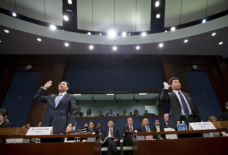 Executives of two major Chinese technology companies, Charles Ding, Huawei Technologies Ltd senior vice president for the U.S., left, and Zhu Jinyun, ZTE Corporation senior vice president for North America and Europe, are sworn in on Capitol Hill in Washington, Thursday, Sept. 13, 2012, prior to testifying before the House Intelligence Committee as lawmakers probe whether their expansion in the U.S. market poses a threat to national security.  (AP Photo/J. Scott Applewhite)