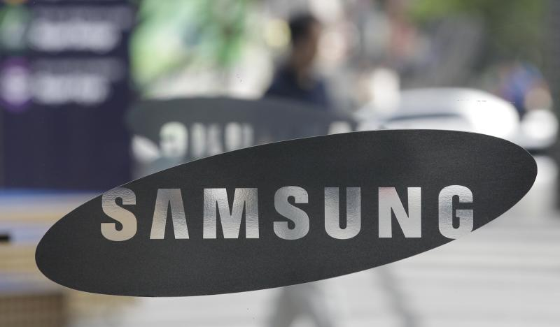 """FILE - In this July 7, 2010 file picture a man walks past near the logos of the Samsung Electronics at its show room in Seoul, South Korea. A Duesseldorf, Germany, court has issued a split decision in a patent dispute between  rivals Apple and Samsung over two of the Korean company's tablet computers.  California-based Apple sued to have sales of both the Samsung Galaxy Tab 10.1N and the Galaxy Tab 7.7 stopped.  But the Duesseldorf state court ruled Tuesday  July 24, 2012 that Samsung made enough changes to the Galaxy Tab 10.1 in its 10.1N that it no longer infringes upon any Apple iPad patents or designs. It said, however, that the back and sides of the smaller Galaxy Tab 7.7 imitated the Apple design in an """"unacceptable manner"""" and ordered European sales stopped.  (AP Photo/ Lee Jin-man,File)"""