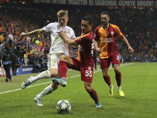 Real Madrid's Toni Kroos, left, duels for the ball with Galatasaray's Yuto Nagatomo during the Champions League group A soccer match between Galatasaray and Real Madrid in Istanbul, Tuesday, Oct. 22, 2019. (AP Photo)
