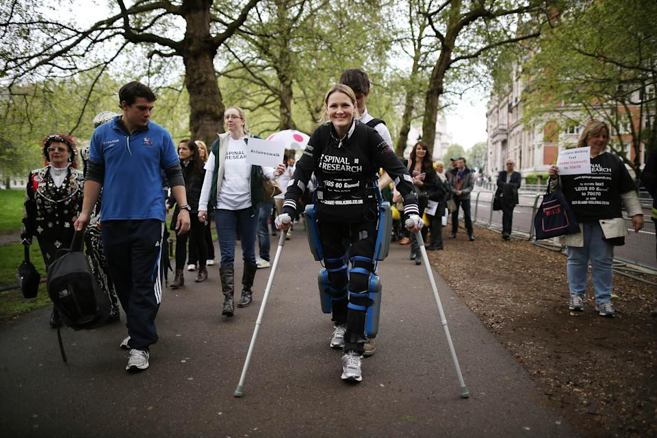 LONDON, ENGLAND - MAY 08: Claire Lomas (C) walks the last mile of the London Marathon on May 8, 2012 in London, England. Ms Lomas, who is paralysed from the waist down after a riding accident in 2007, has taken 16 days to complete the 26.2 mile route. Starting out with 36,000 other runners she has averaged 2 miles a day with the help of a bionic ReWalk suit. (Photo by Peter Macdiarmid/Getty Images)