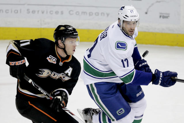 Anaheim Ducks' Saku Koivu, left, of Finland, and Vancouver Canucks' Ryan Kesler look at the puck during the first period of an NHL hockey game on Wednesday, Jan. 15, 2014, in Anaheim, Calif. (AP Photo/Jae C. Hong)