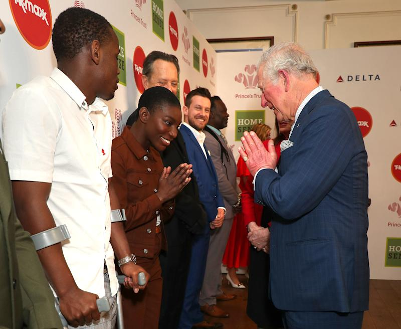 LONDON, ENGLAND - MARCH 11: Prince Charles, Prince of Wales greets Michaela Coel (centre) the Namaste gesture as he attends the Prince's Trust And TK Maxx & Homesense Awards at London Palladium on March 11, 2020 in London, England. (Photo by Yui Mok - WPA Pool/Getty Images)