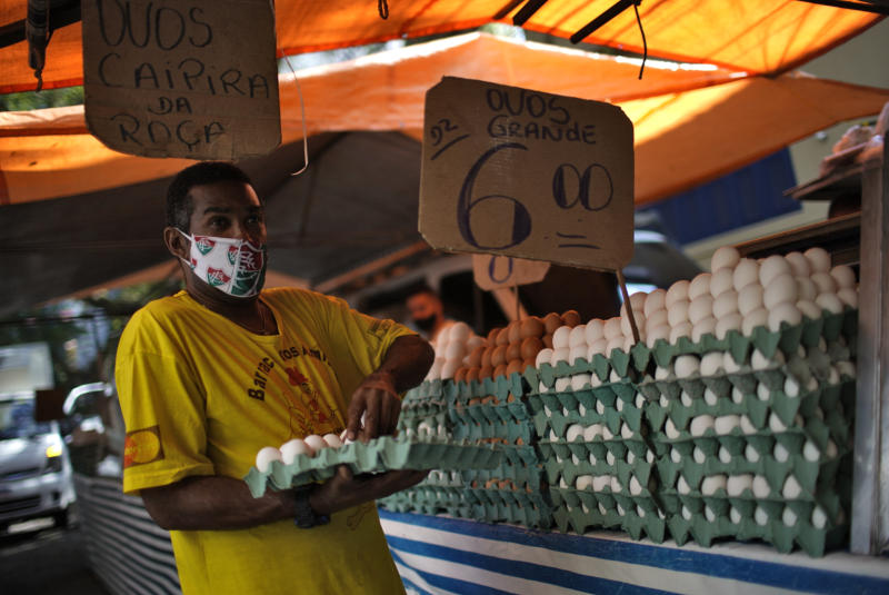 A man wearing a face mask of Brazils football team Fluminense prepares eggs for sale after street markets were reopened in Rio de Janeiro, Brazil on April 29, 2020, amid the new coronavirus pandemic. - Rio de Janeiro's municipality authorized the reopening of street markets but under safety measures as the use of alcohol gel, face masks and keeping a distance of two meters between each stand. (Photo by Mauro Pimentel / AFP) (Photo by MAURO PIMENTEL/AFP via Getty Images)