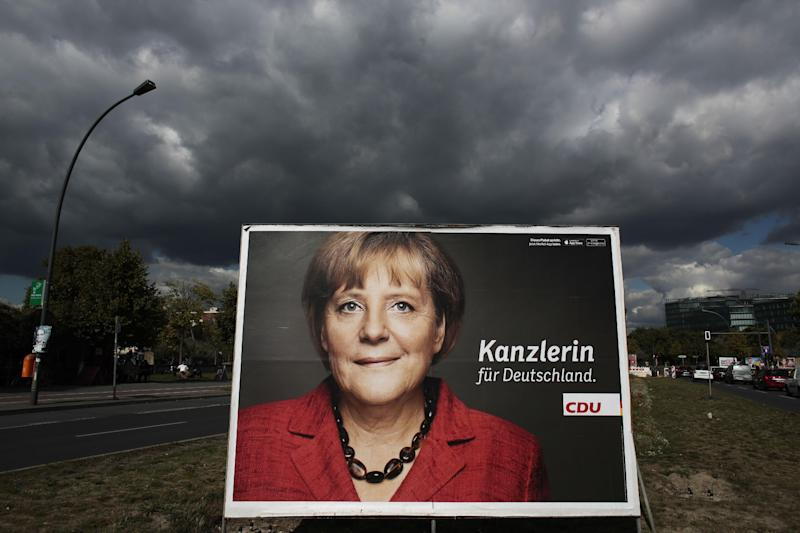 An election campaign poster of German Chancellor Angela Merkel stands in the sun while dark clouds come in on a street in central Berlin, Tuesday, Sept. 17, 2013. Germany faces general elections on Sept. 22, 2013 where Chancellor and Christian Democratic Union (CDU) party chairwoman Angela Merkel will run for her third term . (Words read (Chancellor for Germany. AP Photo/Markus Schreiber)