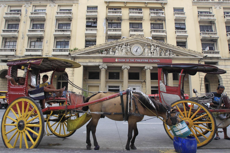 File Photo: A horse cart is parked in front of the Bank of the Philippine Islands in Manila July 1, 2014. (REUTERS/Romeo Ranoco)
