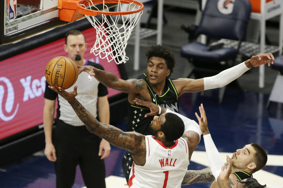 Houston Rockets guard John Wall (1) shoots under pressure from Minnesota Timberwolves forward Anthony Edwards (1) in the first quarter during an NBA basketball game, Friday, March 26, 2021, in Minneapolis. (AP Photo/Andy Clayton-King)
