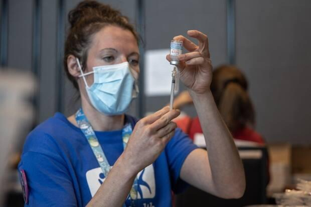 A health-care worker dispenses Moderna vaccine from a vial. As of Monday, 74.3 per cent of Nova Scotians have been fully vaccinated against COVID-19. (Robert Short/CBC - image credit)