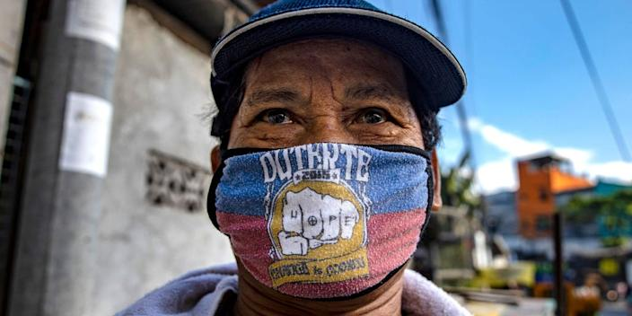 A man is seen wearing a mask with the name of President Duterte and his election campaign slogan on April 5, 2020 in Quezon city, Metro Manila, Philippines.