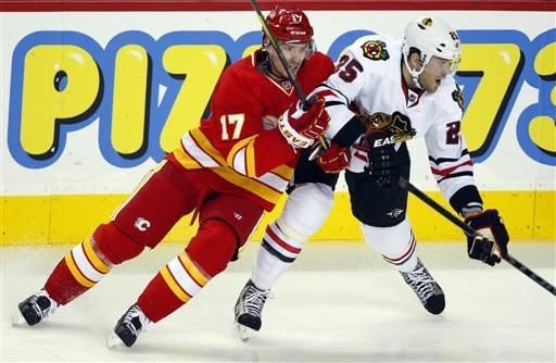 Chicago Blackhawks' Viktor Stalberg, right, from Sweden, collides with Calgary Flames' Blake Comeau during the second period of an NHL hockey game in Calgary, Alberta, Saturday, Feb. 2, 2013. (AP Photo/The Canadian Press, Jeff McIntosh)