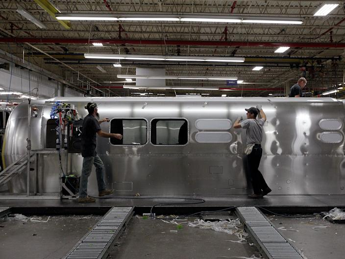 Employees work on an Airstream travel trailer at the Airstream factory Oct. 22, 2014, in Jackson Center, Ohio.