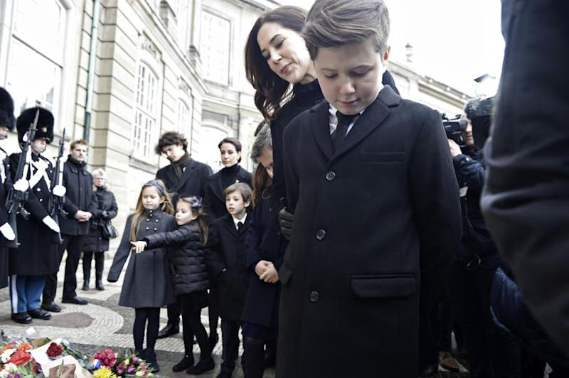 Princess Mary and Prince Christian look over floral tributes to Prince Henrik. Photo: Getty Images