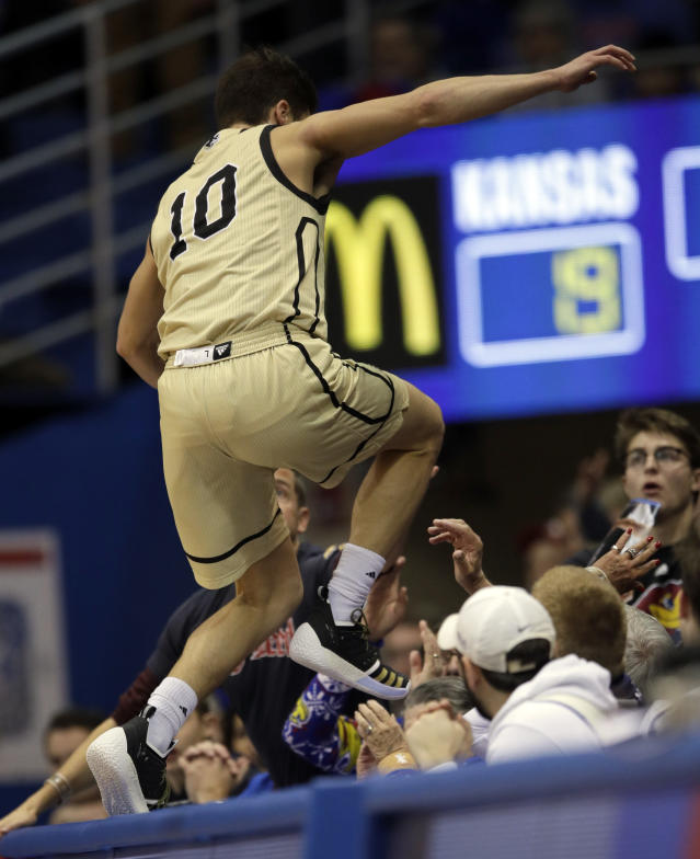 Wofford guard Nathan Hoover (10) jumps over the writer's table during the first half of an NCAA college basketball game against Kansas in Lawrence, Kan., Tuesday, Dec. 4, 2018. (AP Photo/Orlin Wagner)