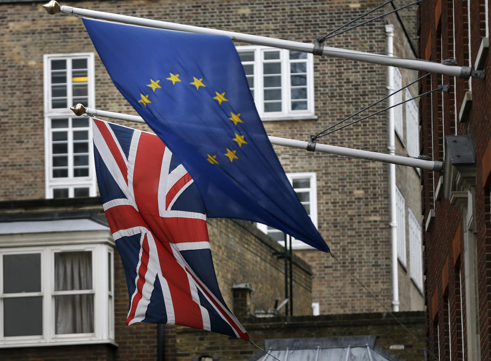 A EU flag hangs beside the Union Jack at the Europa House in London, Wednesday, Feb. 17, 2016. Britain's Prime Minister David Cameron will attend a EU summit starting tomorrow. (AP Photo/Frank Augstein)
