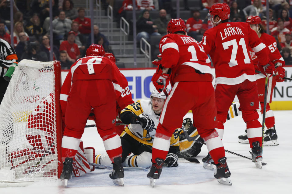 Pittsburgh Penguins left wing Jake Guentzel (59) scores on Detroit Red Wings goaltender Jonathan Bernier (45) in the first period of an NHL hockey game Saturday, Dec. 7, 2019, in Detroit. (AP Photo/Paul Sancya)