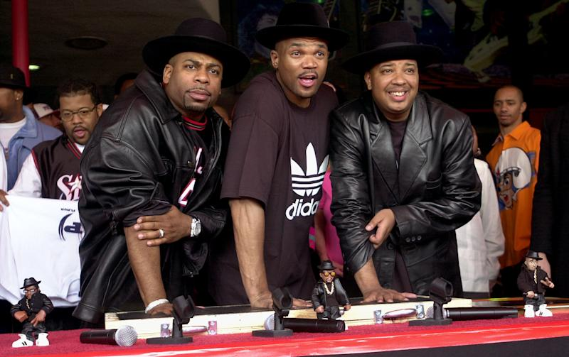 "FILE - This Feb. 25, 2002 file photo shows members of the hip hop group RUN-DMC, from left, Jason ""Jam Master Jay"" Mizell, Darryl ""DMC"" McDaniels and Joseph ""DJ Run"" Simmons creating handprints in cement as they are inducted into Hollywood's RockWalk in Los Angeles.  It was announced Tuesday, July 10, 2012, that McDaniels and Simmons, the surviving members of Run-DMC, will reunite at the Fun Fun Fun Fest in Austin, Texas on Nov. 2-4. Simmons retired from the group after Mizell was shot to death in 2002. Festival organizers say they plan to donate some of the proceeds to the JMJ Foundation for Music, which works to give youth access to the arts. (AP Photo/Krista Niles, file)"