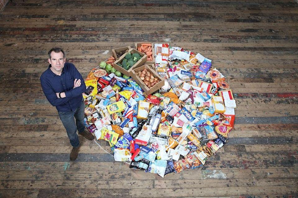 Dr van Tulleken stands next to a pile of food showing the proportion of ultra-processed food compared to fresh food in the average UK diet. — Picture courtesy of BBC Studios