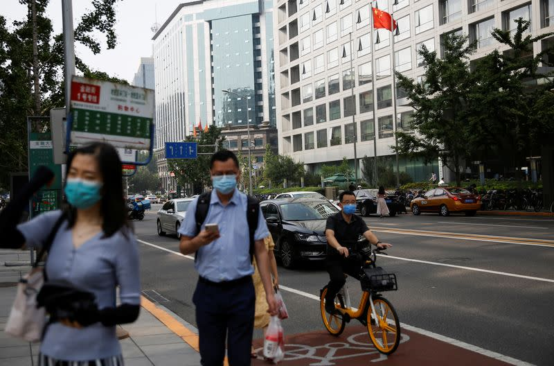 People wearing face masks following the outbreak of the coronavirus disease (COVID-19) walk past a Chinese national flag in front of the building of China Securities Regulatory Commission (CSRC) during morning rush hour, at the Financial Street area in Bei
