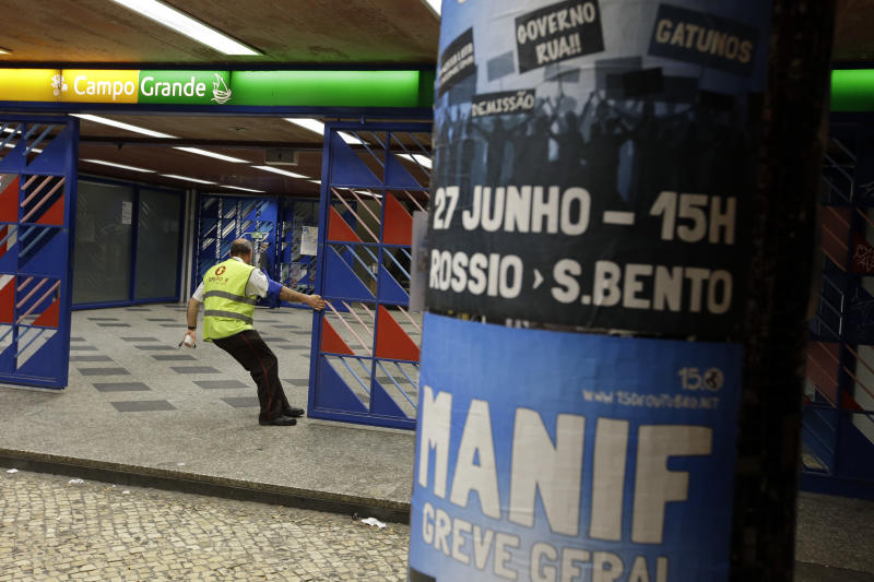 "A security guard closes a gate of a subway station in Lisbon, at the start of a general strike, Wednesday night, June 26 2013. Workers' unions called a 24-hour general strike for June 27 to protest the government's austerity measures and the Lisbon subway will be closed until Friday morning. In the foreground, a poster calls for a demonstration with the words ""Demo, general strike."" (AP Photo/Armando Franca)"