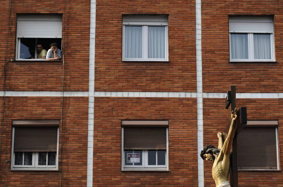 Women look from a window at a crucifix of the Christ of the Compassion during a procession that marks the beginning of Holy Week in Oviedo, northern Spain.