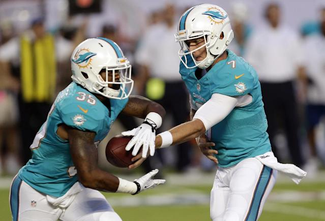 Miami Dolphins quarterback Pat Devlin (7) hand off the ball to running back Mike Gillislee (35) during the first half of an NFL preseason football game against the New Orleans Saints, Thursday, Aug. 29, 2013, in Miami Gardens, Fla. (AP Photo/Wilfredo Lee)