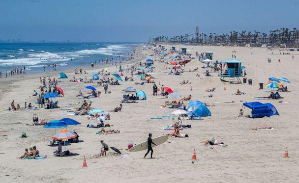 PHOTO: Some beach-goers wear masks while others don't outside while recreating at the pier on Monday, July 20, 2020, in Huntington Beach, Calif. (Allen J Schaben/Los Angeles Times via Shutterstock)