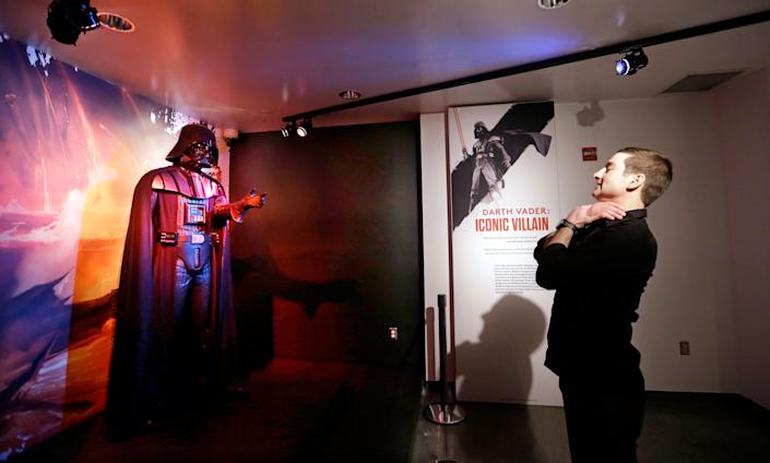Project director Saul Drake stands-in where visitors are likely to want their photo taken in front of a Darth Vader costume on display. (AP Photo/Elaine Thompson)