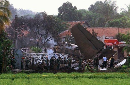 Emergency personnel look through the rubble after an Indonesian military Fokker-27 aircraft crashed in Jakarta on June 21. The number of people killed when the jet crashed into a housing complex has risen to 11, an air force spokesman said Friday