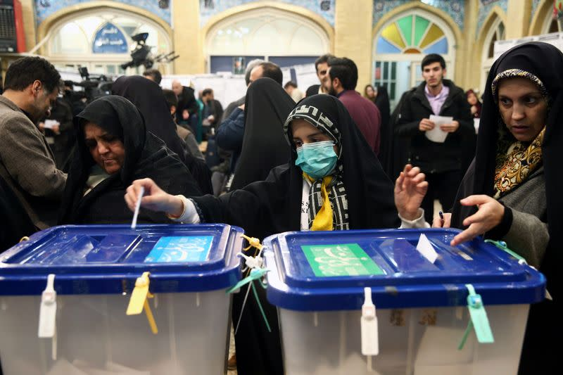 Woman wears a face mask as she casts her vote during parliamentary elections at a polling station in Tehran