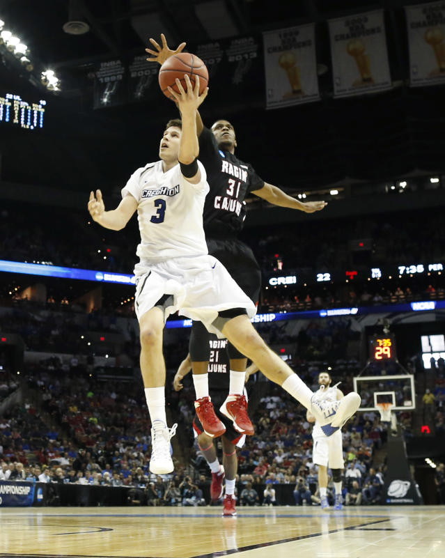 Creighton's Doug McDermott (3) shoots past Louisiana-Lafayette's Kevin Brown (31) during the first half of a second-round game in the NCAA college basketball tournament Friday, March 21, 2014, in San Antonio. (AP Photo/David J. Phillip)