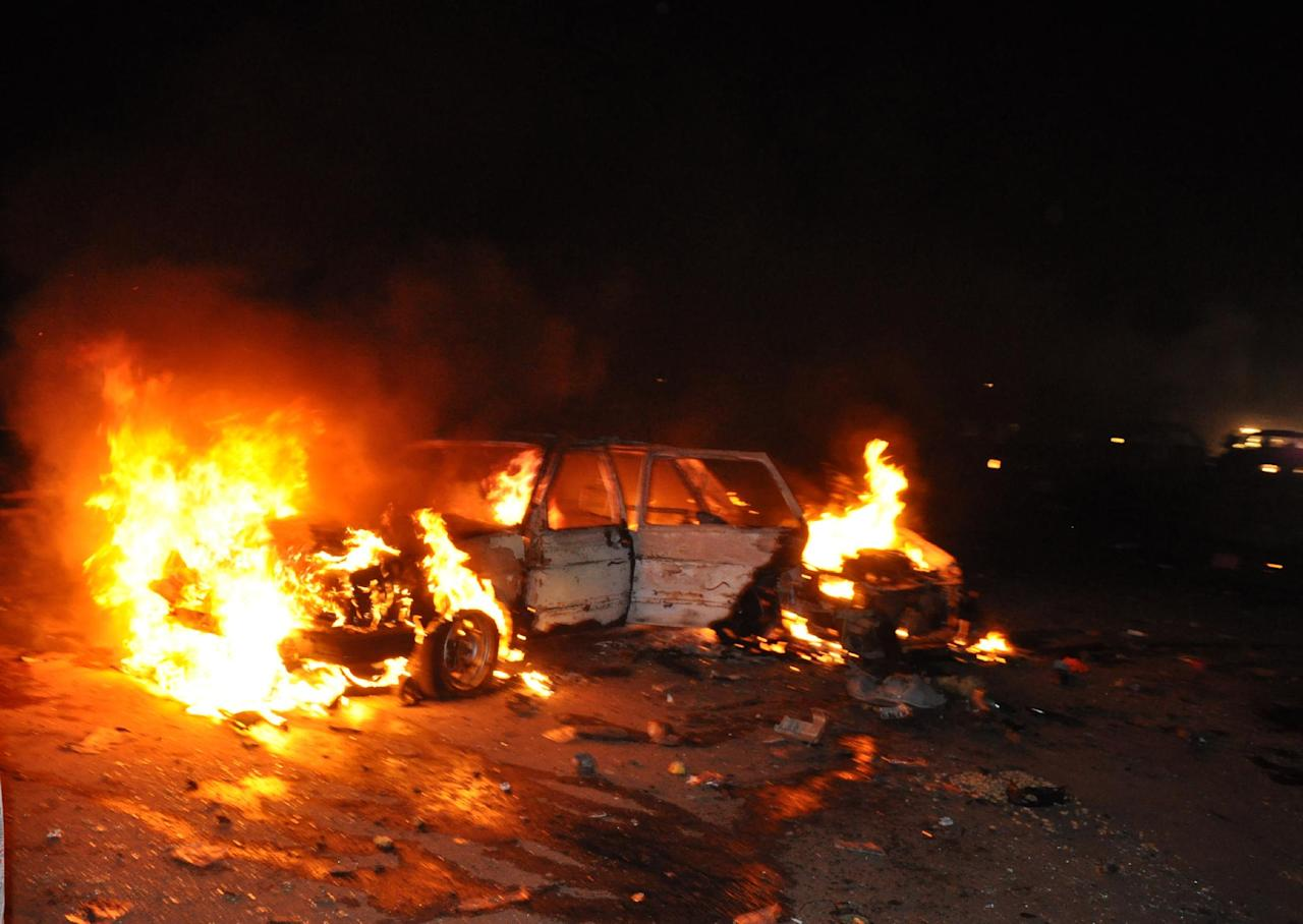 A car burns following a bomb explosion in Abuja, Nigeria, Thursday, May 1, 2014. A car bomb exploded on a busy road in Nigeria's capital late Thursday, killing at least 12 people days before the city is to host a major international economic forum. (AP Photo/Gbemiga Olamikan)