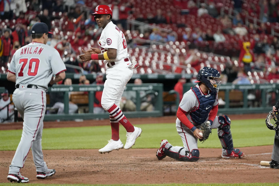 St. Louis Cardinals' Justin Williams, center, celebrates after scoring past Washington Nationals catcher Alex Avila, right, as Nationals pitcher Luis Avilan (70) watch during the fifth inning of a baseball game Tuesday, April 13, 2021, in St. Louis. (AP Photo/Jeff Roberson)