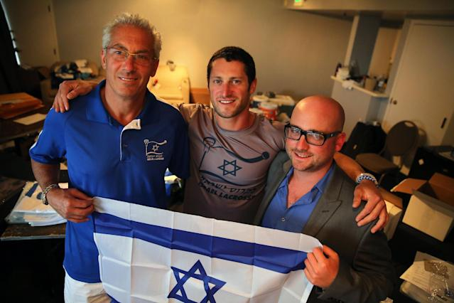 In this July 15, 2014 photo, Israel Lacrosse head coach Bill Beroza, left, attackman Noach Milller, center, and team executive director Scott Neiss hold an Israeli flag inside a hotel room used to organize team gear, in Commerce City, Colo. In its first tournament appearance, the Israeli lacrosse team is handily defeating opponents in the Lacrosse World Championship, even as its players' minds are on their homeland. (AP Photo/Brennan Linsley)