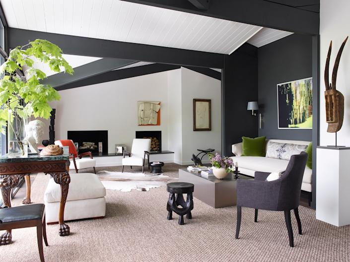 """<div class=""""caption""""> Smyth traded in the living area's original stone fireplace for a sleek and simple version. """"It was very dated,"""" he says of the previous incarnation. An African mask from <a href=""""https://sutterantiques.com/"""" rel=""""nofollow noopener"""" target=""""_blank"""" data-ylk=""""slk:Sutter Antiques"""" class=""""link rapid-noclick-resp"""">Sutter Antiques</a> and a vintage Indian stool from <a href=""""https://store.comerfordcollection.com/"""" rel=""""nofollow noopener"""" target=""""_blank"""" data-ylk=""""slk:Comerford Collection"""" class=""""link rapid-noclick-resp"""">Comerford Collection</a> lend interest to the streamlined seating. The abstract photo above the sofa is by Smyth. </div>"""