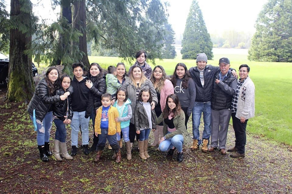 In this undated photo provided by Melissa Espinoza, Raul Espinoza Gomez, second from right, poses for a photo at Remlinger Farms, in Carnation, Wash., where the majority of the family works. He's pictured with some of his 22 grandchildren and great-grandchildren. Gomez has an appointment Saturday, March 6, 2021, for his second dose of coronavirus vaccine and by Easter, the 77-year-old's immune system will be ready to protect him from the virus. But how the family celebrates will depend on government advice, Melissa Espinoza said. (Melissa Espinoza via AP)