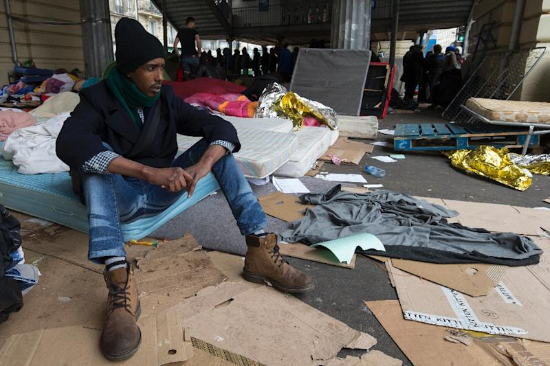A migrant sits on a mattress at a makeshift camp in Paris on March 24, 2016