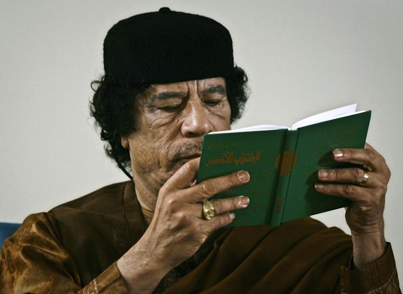 "FILE - In this Friday, March 2, 2007 file photo, Libya's Moammar Gadhafi holds a copy of the Green Book during a debate on the sidelines of celebrations marking the 30-year anniversary of the declaration of the ""jamahiriya,"" or ""rule of the masses"", in Sabha, Libya.  A new law that excludes former officials of the Moammar Gadhafi era from public office is dividing Libya and deepening the turmoil that has plagued the country since the civil war that ousted the erratic leader. Passed by lawmakers essentially at gunpoint, it bans not just those who held office but even clerics who glorified the dictator and researchers who worked on his notorious political tract, the Green Book. (AP Photo/Nasser Nasser, File)"
