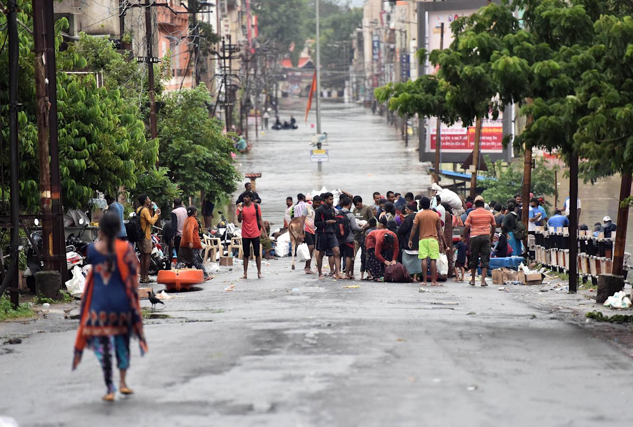 SANGLI, INDIA - AUGUST 9: Stranded people wait for boats in flood in Sangli, on August 9, 2019 in Sangli, India. Teams of the National Disaster Response Force, Indian Army and Navy continued evacuating people to safer locations in boats in coordination with the local administration. Despite decrease in the intensity of rainfall, the flood situation in Sangli and Kolhapur continues to be serious with the death toll rising to 27, including nine persons who died as the private rescue boat carrying them overturned in Bramhnal village in Palus taluka of Sangli district. (Photo by Pratham Gokhale/Hindustan Times via Getty Images)