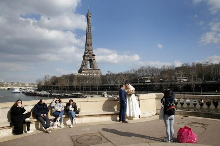 A newly married couple poses in front of the Eiffel Tower during the Coronavirus pandemic on February 26, 2021 in Paris, France.