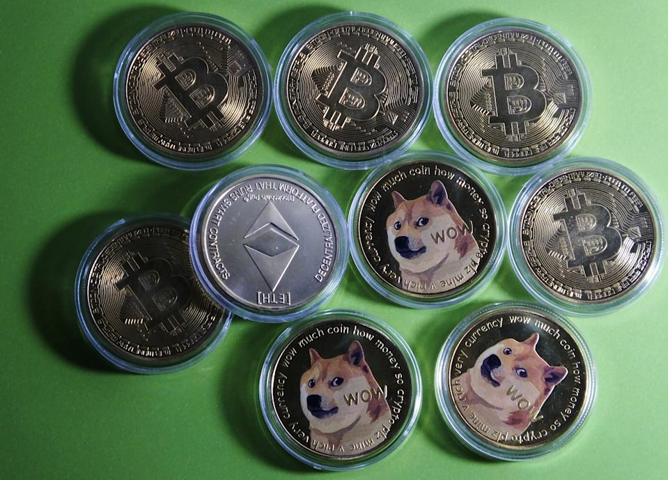 Bitcoin, Dogecoin and Ethereum physical commemorative coins are displayed in Yichang, Hubei Province, China. Photo: Costfoto/Barcroft Media via Getty Images