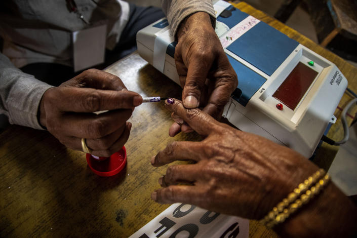 A polling officer applies indelible ink on a voter's finger at a polling station during the third phase of assembly election in Gauhati, India, Tuesday, April 6, 2021. (AP Photo/Anupam Nath)