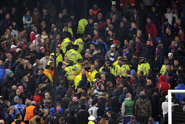 Police move in amongst the CSKA Moscow fans during the Champions League Group D soccer match between Manchester City and CSKA Moscow at the Etihad Stadium in Manchester, England, Tuesday, Nov. 5, 2013. (AP Photo/Clint Hughes)