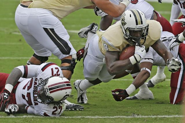 Central Florida running back Storm Johnson (8) dives across the goal line for a 1-yard touchdown past South Carolina cornerback Victor Hampton (27) during the first half of an NCAA college football game in Orlando, Fla., Saturday, Sept. 28, 2013.(AP Photo/John Raoux)