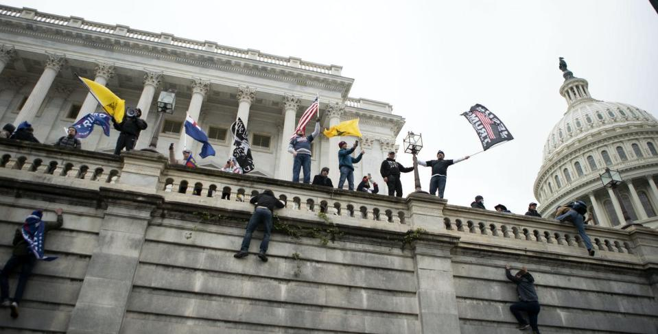 """<span class=""""caption"""">Supporters of U.S. President Donald Trump climb the west wall of the the U.S. Capitol on Jan. 6, 2021, in Washington. </span> <span class=""""attribution""""><span class=""""source"""">(AP Photo/Jose Luis Magana)</span></span>"""