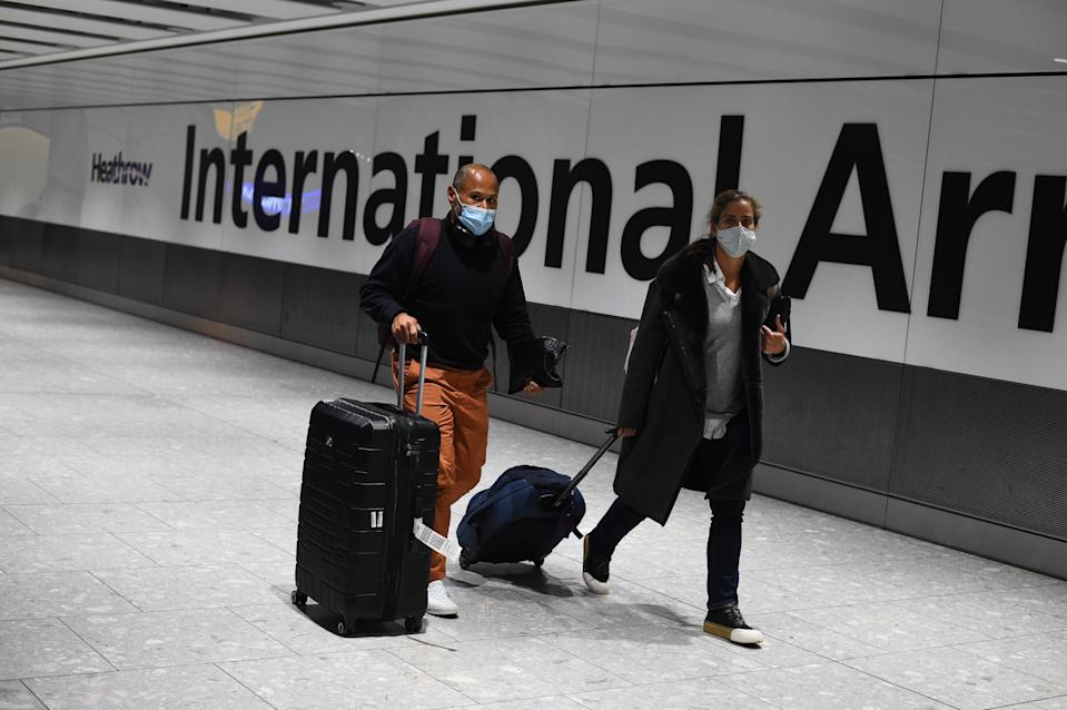 Passengers walk with luggage through the Arrival Hall of Terminal 5 at London's Heathrow Airport after arriving into the UK following the suspension of the travel corridors. Passengers arriving from anywhere outside the UK, Ireland, the Channel Islands or the Isle of Man must have proof of a negative coronavirus test and self-isolate for 10 days. Picture date: Monday January 18, 2021.