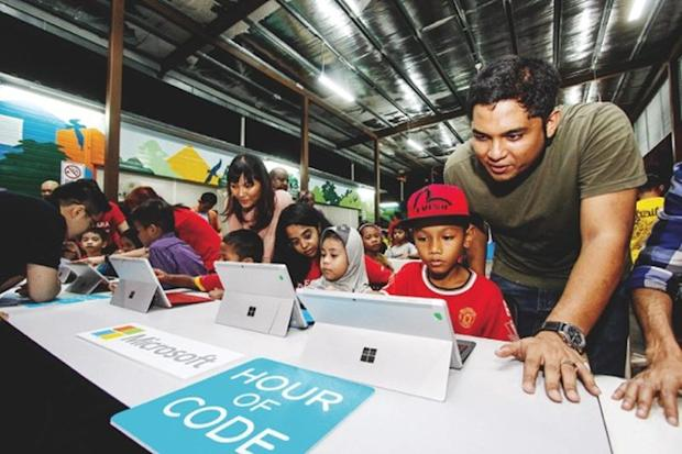 Alif Hakimi Helmi (right) and other children get a feel of the Microsoft tablet. ― Picture by Hari Anggara