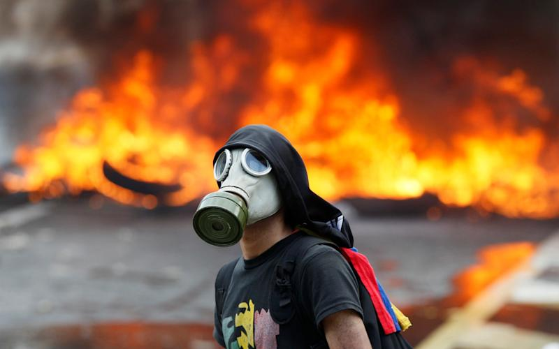An anti-government protester stands in front of burning barricade on a highway in Caracas - AP