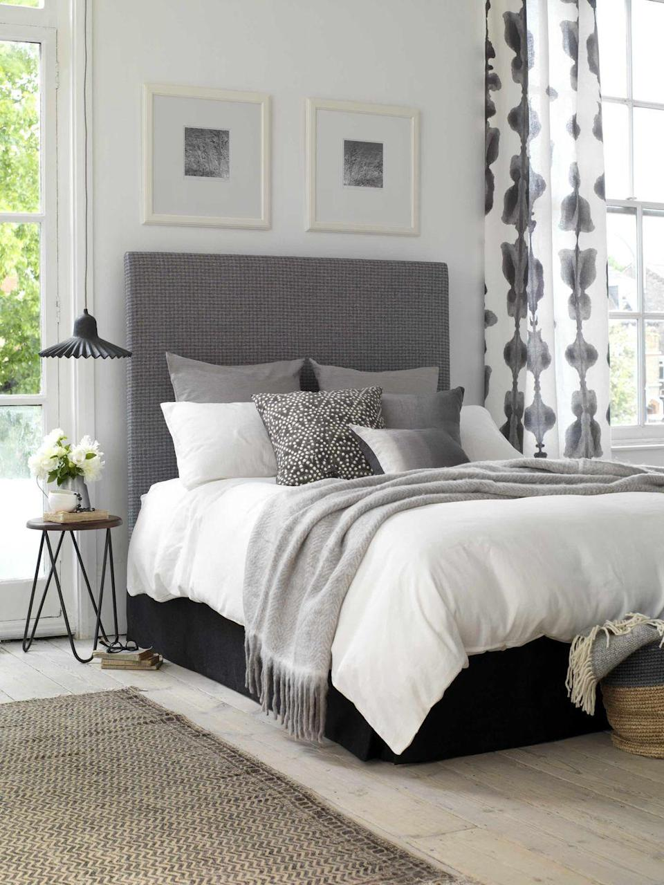 """<p>To introduce grey to a plain bedroom, start with the bed. A tall headboard has impact and immediately anchors the space. Then adding grey prints above create symmetry. Add a bold grey and white patterned curtain, grey cushions and throws, and a black pendant light for a complete look.</p><p>Top tip: Siting a bed between two windows gives it a frame and makes it easier to create your look.</p><p>Pictured: <a href=""""https://www.buttonandsprung.com/upholstered-beds/lavender/"""" rel=""""nofollow noopener"""" target=""""_blank"""" data-ylk=""""slk:Lavender double divan, Button & Sprung"""" class=""""link rapid-noclick-resp"""">Lavender double divan, Button & Sprung</a></p>"""