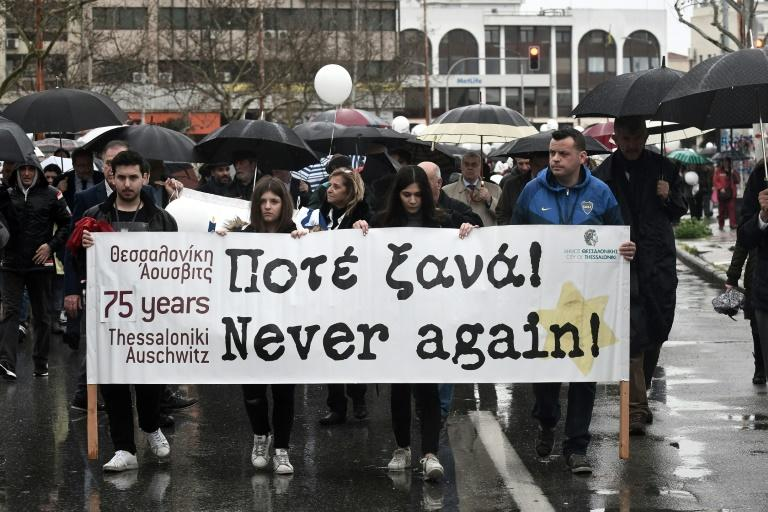 "People walk to the old railway station in Thessaloniki bearing banners urging ""never again"" as they remember the city's deported Jews, 75 years on"
